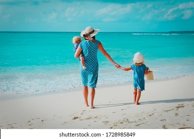 family on beach vacation-mother with two kids at sea