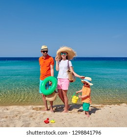 Family on beach wearing straw sun hat. Young couple with three year old boy, holding inflatable ring, beach bag and bucket toy. Clear sky. Summer family vacation. Sithonia, Greece.