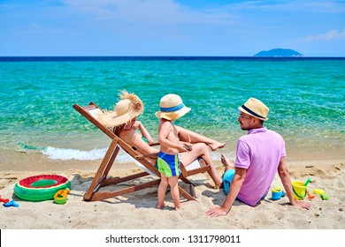 Family on beach, young couple with three year old boy. Summer family vacation. Sithonia, Greece.