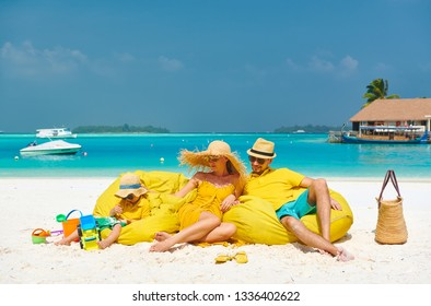 Family on beach, young couple in yellow with three year old boy. Summer vacation at Maldives.
