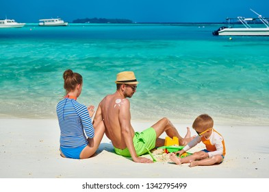Family on beach, young couple with three year old boy. Woman applying sun screen protection lotion on man's back. Summer vacation at Maldives.