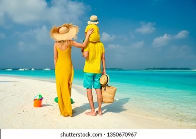 Familia en la playa, pareja joven en amarillo con niño de tres años. Vacaciones de verano en Maldivas.