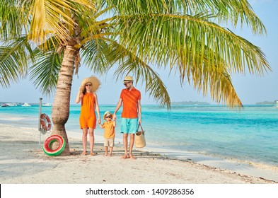 Family on beach, young couple in orange with three year old boy under the palm tree. Summer vacation at Maldives.