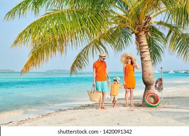Familia en la playa, pareja joven de naranja con niño de tres años bajo la palmera. Vacaciones de verano en Maldivas.