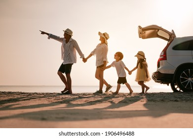 Family on the beach.Vacation time. Happy father, mother and son enjoying road trip the summer holidays.Parents and children are sitting on a hatchback with a sea background.