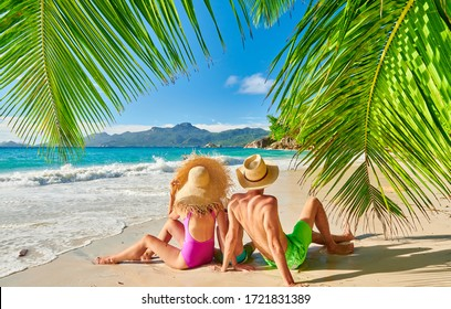 Family on beautiful Anse Soleil beach with palm tree, young couple with three year old toddler boy. Summer vacation at Seychelles, Mahe.