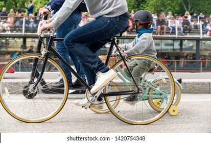 A family on a bicycles pedals a bikes, preferring an active healthy lifestyle using cycling and alternative environmentally friendly mode of transport in order to preserve the Paris environment