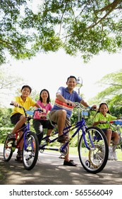 Family, on bicycles, portrait, low angle view