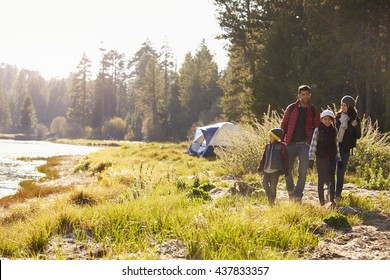 Family on a camping trip walking near a lake