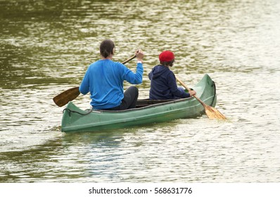 Family on canoe tour. Father and child paddling in kayak in a lake on a sunny day.