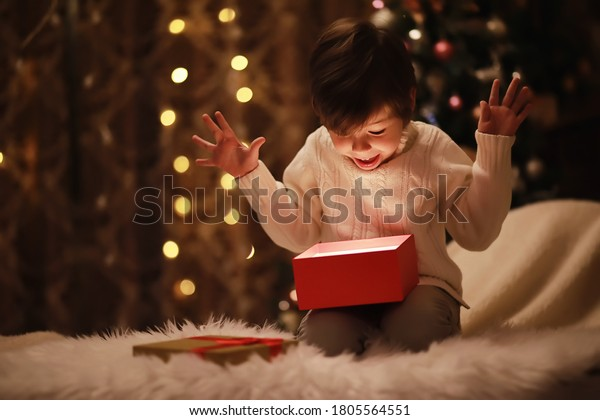 Family on Christmas eve at fireplace. Kids opening Xmas presents. Children under Christmas tree with gift boxes. Decorated living room with traditional fire place. Cozy warm winter evening home.