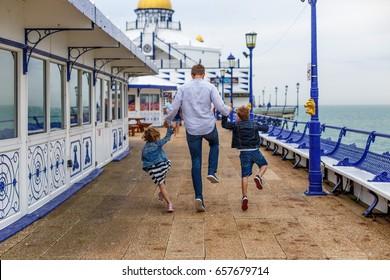 Family on Eastbourne pier in spring, UK