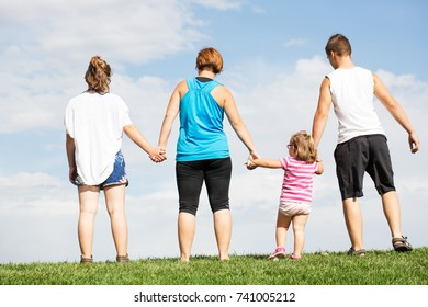 Family on herb under blue sky with clouds
