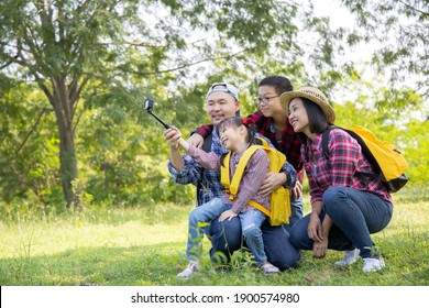 Family on hike in a forest taking selfie group portrait.Travel vacations and life concept