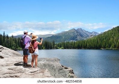 Family on hiking trip. Father and daughter taking photos of beautiful mountains with iphones. Bear Lake, Rocky Mountains National Park, Colorado, USA.