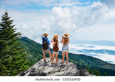 Family on hiking trip, standing on top of the mountain over the clouds, looking at beautiful summer mountain  landscape. People enjoying beautiful view. Close to Asheville, North Carolina, USA.