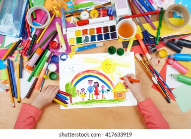 family on meadow with rainbow and house child drawing, top view hands with pencil painting picture on paper, artwork workplace