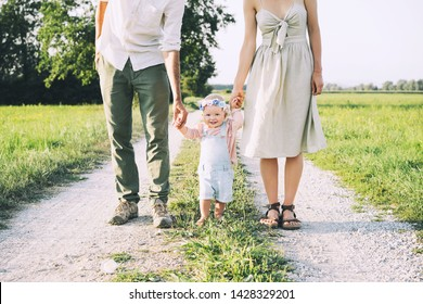 Family on nature at summer. Mother and father with one year old baby girl outdoors. Woman and man with child in countryside. Photo of natural parenthood, slow fashion, conscious life, eco lifestyle.