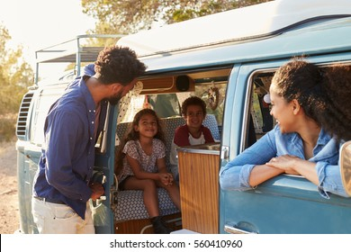Family on a road trip making a stop in their camper van