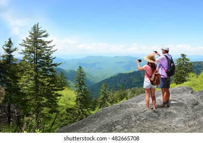 Family on  summer hiking  trip  trip enjoying time together. Father and daughter on top of mountain  taking photos of beautiful mountains with iphones. North Carolina, USA.