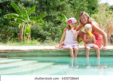 Family on summer holiday villa swimming pool edge together enjoying vacation abroad, sunny outdoors. Mother with children eating lollies ice creams, fun activities, leisure recreation lifestyle.