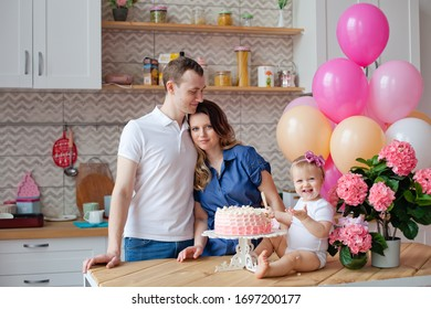 family on the table with a birthday cake and balloons