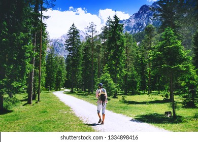 Family on trekking day in the mountains. Mother and child on nature. Tourists travel at Dolomites, Italy, Europe. Summer holiday in South Tyrol. Woman hiking with baby in carrier backpack