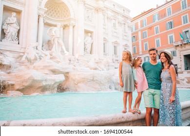 Family on vacation against Trevi Fountain Fontana di Trevi in Rome, Italy.