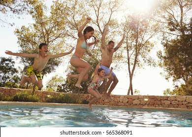 Family On Vacation Jumping Into Outdoor Pool