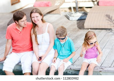 Family on vacation sitting by the pool at their villa