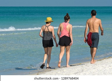 Family on vacation taking a leisure walk on on the Beach and enjoying a beautiful sunny day on the Gulf Coast of Florida.