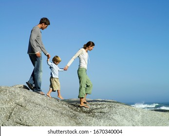 Family on vacation walking on rocky beach overlooking Atlantic Ocean