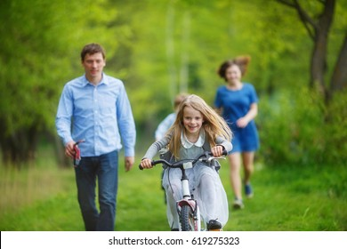 Family on a walk in the forest. A girl rushes on a bicycle on the green grass, parents try to catch up with her on foot