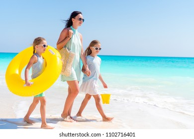 Family on white beach. Mother with kids going to swim in the sea