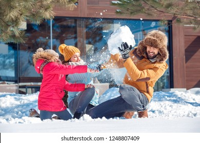 Family on a winter vacation spending time together outdoors sitting mother and daughter throwing snow fighting while father holding big snowball up laughing surprised close-up