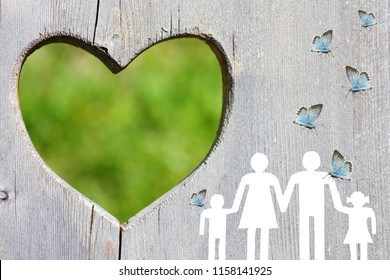 Family on wooden background with green heart and blue butterflies welfare concept