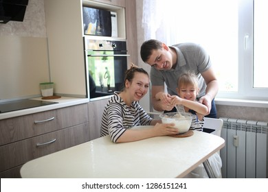 family with one child amicably cooked together in the kitchen, the daughter helps her parents.