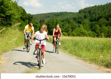 Family with one child riding their bicycles on a summer day (focus on the girl in front)