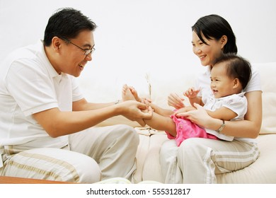 Family with one child sitting face to face, father holding daughter's leg