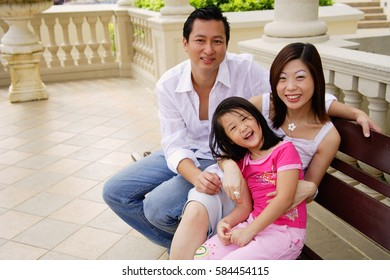 Family with one child, sitting on bench, looking up at camera