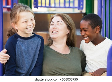 Family of one mother and two sons laughing together at park