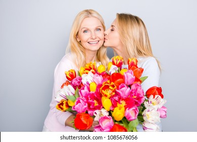 Family with one parent, stylish trendy cheerful daughter congratulate her charming mother  presenting big bouquet of colorful tulips kissing in cheek isolated on grey background