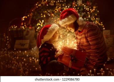 Familienöffnen Weihnachtsbeleuchtung Geschenkbox vor Weihnachtsbaum, Glückliche Mutter mit Baby Kind in Magic Night