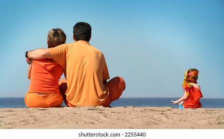 Family in orange clothes on the beach