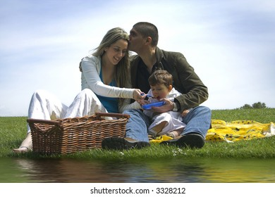 family outdoor in a field near water having a picnic