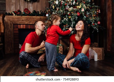 family in pajamas plays next to a Christmas tree and a fireplace. A little girl with a tassel draws at Mom's face, Dad looks. Polythra on the floor. Red T-shirts.