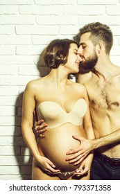 family parent couple of pretty happy sexy woman or cute pregnant girl with round belly in bra and handsome bearded man hipster with slim bare torso and chest on brick wall background at mothers day