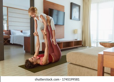 Family. Parent And Kid Doing Partner Yoga At Home. Sporty Child And Mother Practicing Acroyoga In Living Room. Young Woman And Daughter Exercising Together.
