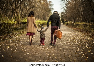family, parenthood, adoption and people concept - happy mother, father and little girl walking in summer park