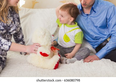 Family, parenthood and children concept - Close-up of happy mother, father and son playing together with teddy bear on bed in bedroom at home.